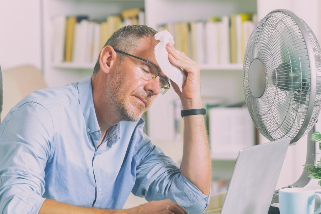 man suffering from extreme hot temperature in his office