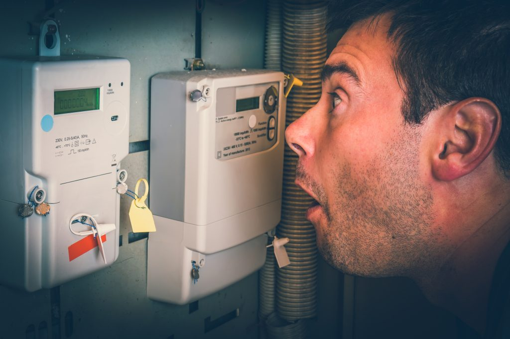 man looking at electric meter terrified